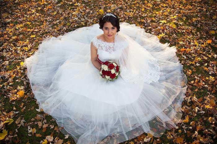 Braut auf einer Wiese mit buntem Herbstlaub