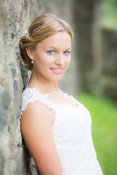 Hochzeitsfotografie - Junge Frau lehnt an einem Baumstamm